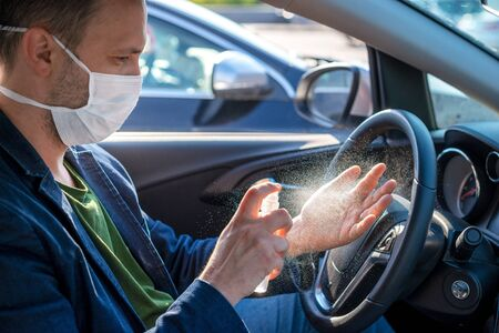 Spraying anti-bacterial sanitizer spray on hand in car, infection control concept. Imagens