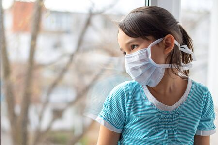 Adorable sad child girl in medical mask by the window at home. Quarantine. Coronavirus pandemic.