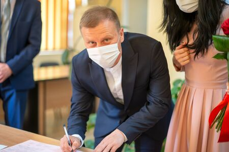 Galati, Romania - April 10, 2020:Couple in love just married in covid pandemic. Signing wedding certificate