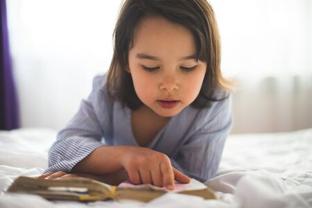 Little girl reading from bible while she is in bed in the morning