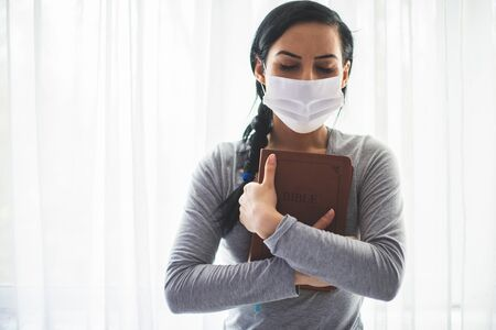Portrait of a woman with a surgical mask on her face and a bible held tight to her chest Imagens