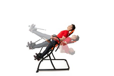 Man doing exercise on inversion table for his back pain, isolated on white. Multiple positions. Stock fotó