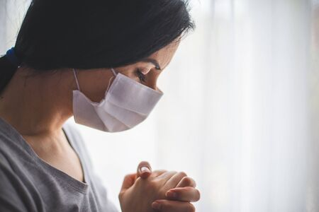 Portrait of woman with surgical mask praying next to window Imagens