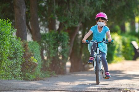 Little girl in protective medical mask rides a bicycle. Imagens