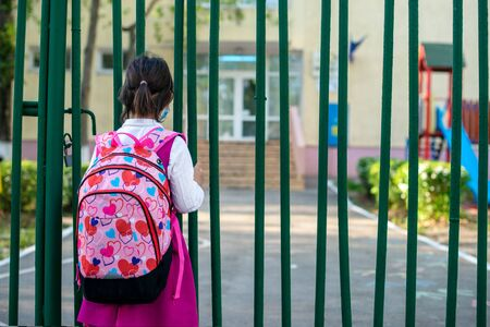 Little school girl sitting next to school fence waiting for going back to clases after pandemic outbreak Imagens