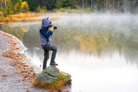 Creative child, kid photographer (a little boy) with a camera taking landscape pictures near la lake