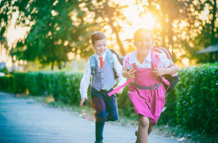 Two little schoolchildren are happy to meet again at the beginning of a new school year
