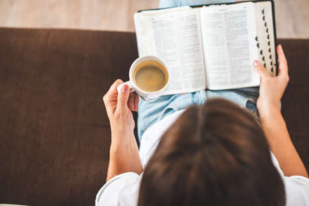 Woman hand holding cup of coffee and reading Holy bible. 版權商用圖片 - 155192287