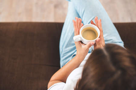 Top view of Caucasian young woman holding coffee cup while sitting on sofa at home