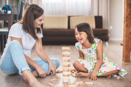 Young mother with her little daughter play game in wood block 版權商用圖片 - 155292883