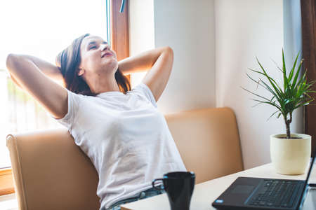 Calm smilin woman relaxing with  hands behind head, happy woman resting  satisfied after work done, enjoying break with eyes closed, peace of mind, no stress 版權商用圖片