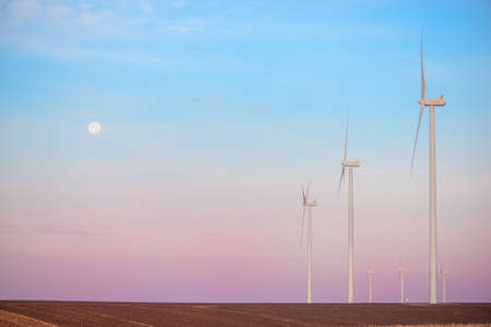 Windmills for electric power production at sunset