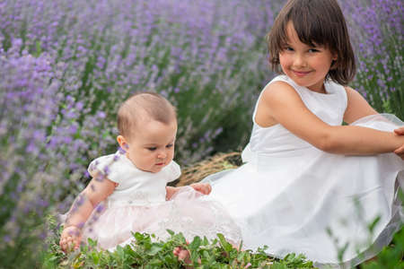 Family portrait in lavender field, two sisters together having fun