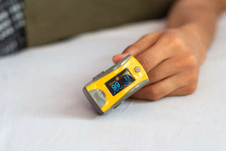 Close-up of woman's hand resting on bed, wearing pulse oximeter to measure blood oxygen saturation Фото со стока