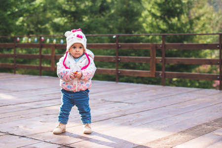 Small adorable infant standing on all fours on wooden floor at home.