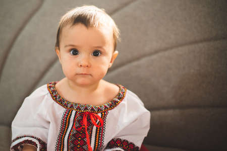 Portrait of cute infant baby girl wearing a traditional Romanian costume