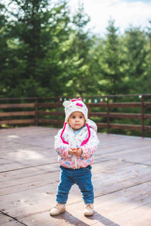 Portrait of little toddler girl walking and having fun outdoors in cold weather at mountains