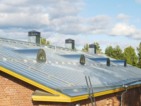 lowrise: New steel pitched roof with water drain system and air ducts. Stock Photo