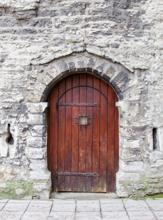 archway: Old wooden arched door in stone wall. Stock Photo