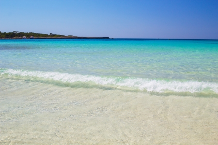 Crystal clear water and white sand at Cala Son Saura beach, Menorca island, Spain
