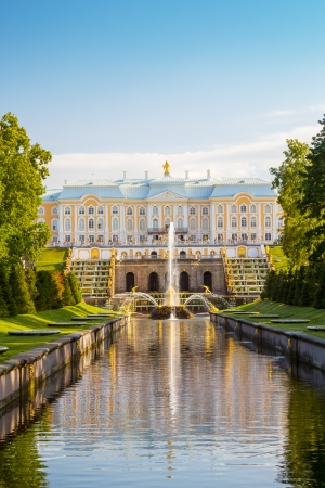 The Peterhof Grand Palace with reflection in the main park channel, Saint-Petersburg, Russia  It was built in 1714 as a country residence of Peter The Great  Stock Photo - 23970128