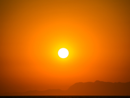 sea background: Orange summer heat sunset with mountains silhouette.