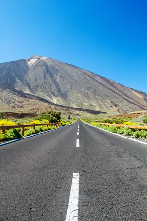 foreground focus: Old cracked country asphalt road background with focus on foreground and blurred landscape.
