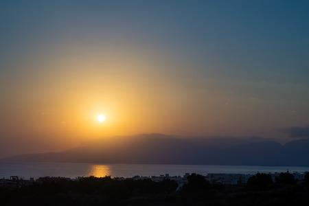 kreta: Hersonissos foggy sunrise with sun glade, Crete, Greece.