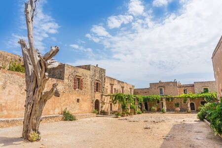 ida: Arkadi Monastery inner yard with the old dead cypress tree with bullet holes at Crete, Greece. It was founded in the beginning of the 14th century and almost destructed by the Ottomans in 1866.