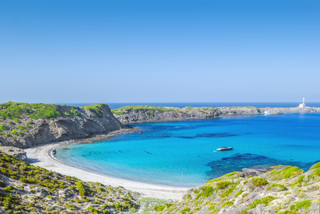 Cala Presili beach with the view on Raco de sAlga Morta and Faro de Favaritx on a sunny summer day, Menorca island, Balearic islands, Spain. Reklamní fotografie