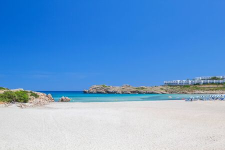 menorca: Arenal de Son Saura beach with white sand and turquoise Mediterranean sea in summer sunny day at Menorca island, Spain. Stock Photo