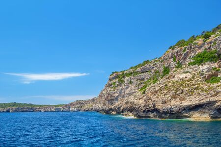 Menorca island coast with the cliffs covered with green bushes, Balearic islands, Spain.