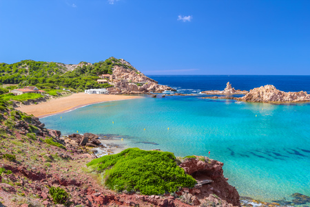 Cala Pregonda beach with golden sand on summer sunny day at Menorca island, Balearic islands, Spain. Imagens - 63247185