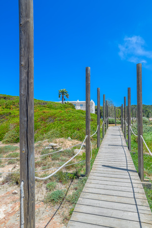Wooden path to Playa de Son Bou Beach on sunny summer day at Menorca island, Spain. Travel background. Stock Photo