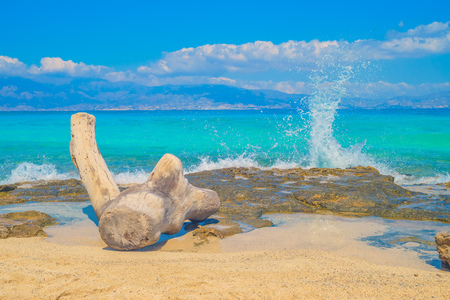 Chrisi (Chrysi) island beach water splash background with old wooden log. Popular place for taking photos. Greece.