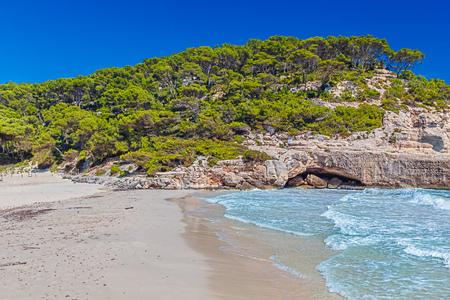 Cala Mitjana Beach on Sunny Day. Menorca Island, Spain. Banco de Imagens