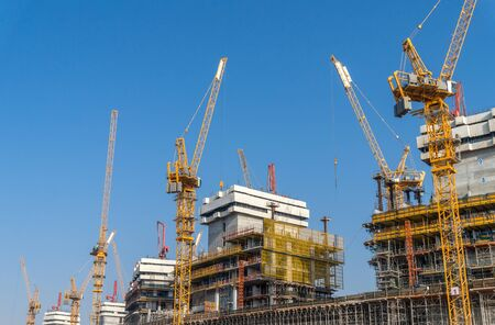 Construction Site with Tall Tower Cranes and Concrete Building Frames. Construction Background.