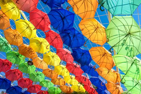 Colorful Umbrellas Hanging in the Air above the City Street. Colorful Summer Background. Rows of Color Umbrellas Protecting from Sunlight. Stockfoto