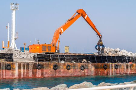 Sea Shore Reinforcement Works with Excavator Standing on Floating Platform.