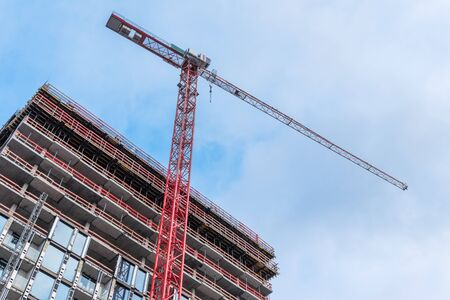 Construction Site with Tall Tower Crane and Concrete Building Frame. Construction Background. Stockfoto