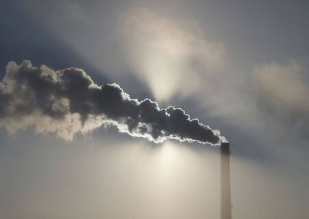 Morning sun through black smoke from chimney of factory