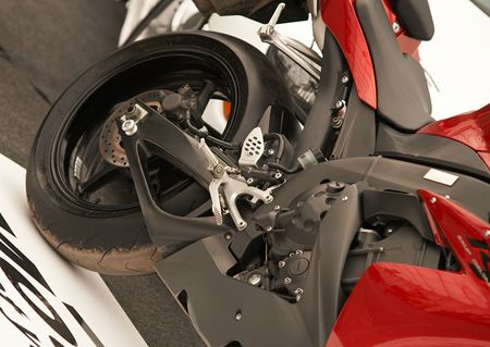 Red  and black motorbike wheel and engine detail, close-up