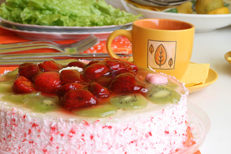 Cake with strawberries and kiwi slices and coffee cup photo