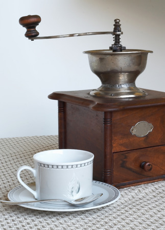 hiss: Coffee grinder and one white cup of coffee Stock Photo