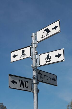 directional sign for swimming and camping against a clear blue sky