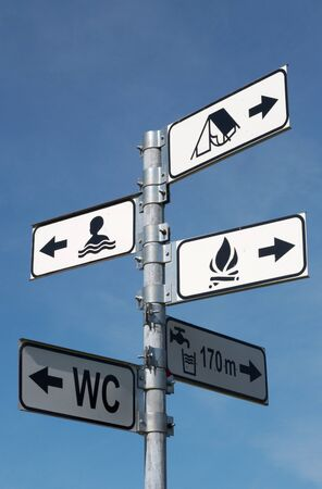 directional sign for swimming and camping against a clear blue sky photo
