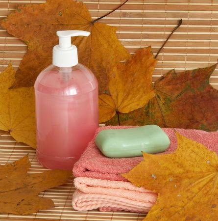 Liquid soap dispenser and soap on bamboo background photo