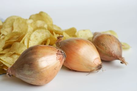 pealing: Close-up of three yellow onions and potatoe chips on background Stock Photo