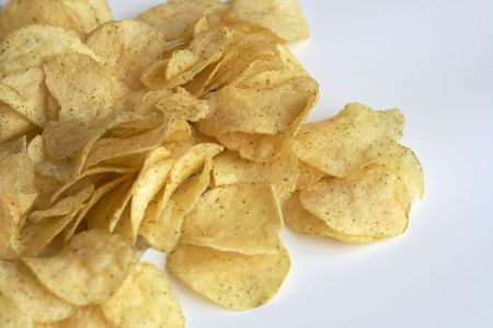 gease: Heap of fried potato chips on white background.