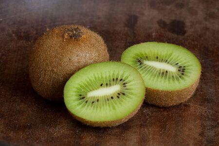 Sliced kiwi fruits on dark wooden background